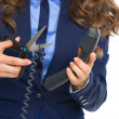 Closeup on business woman cutting phone wire — Stock Photo