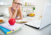 Smiling young woman studying in kitchen — Stock Photo