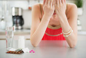 Feeling bad girl and pills on table — Stock Photo