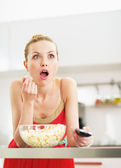 Surprised young woman eating popcorn and watching tv in kitchen — Stock Photo