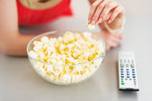 Closeup on teenager girl eating popcorn and watching tv — Stock Photo