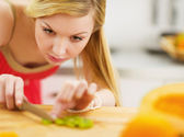 Young woman cutting salad in kitchen — Stock Photo