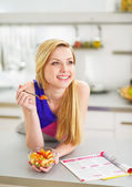 Smiling young woman eating fruits salad in kitchen — Stock Photo