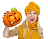 Young woman in hat and scarf scaring with jack-o-lantern — Stock Photo