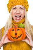 Young woman in hat and scarf with jack-o-lantern — Stock Photo