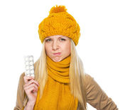 Frustrated young woman in hat and scarf with pack of pills — Stock Photo