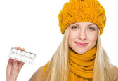 Happy young woman in hat and scarf showing pack of pills — Stock Photo