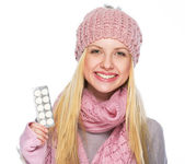 Happy teenager girl in winter hat and scarf showing pills pack — Stock Photo