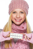 Portrait of smiling teenager girl in winter hat and scarf showin — Stock Photo