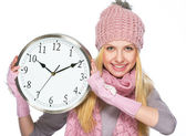 Happy teenager girl in winter hat and scarf showing clock — Stock Photo