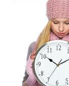 Teenager girl in winter hat and scarf showing clock — Stock Photo