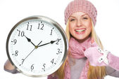 Happy teenager girl in winter hat and scarf showing clock and th — Stock Photo