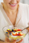 Closeup on young woman eating fresh fruits salad — Stockfoto