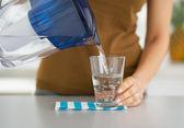 Gros plan sur femme au foyer en versant l'eau dans le verre du filtre à eau — Photo