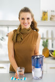 Happy young housewife with glass of water and water filter pitch — Stock Photo