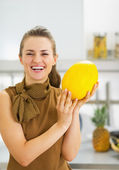 Smiling young woman holding melon — Stockfoto