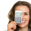 Happy business woman holding calculator in front of face — Stock Photo #30050185