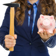 Closeup on business woman giving piggy bank and hammer — Stock Photo