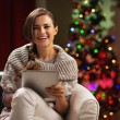 Smiling young woman near christmas tree using tablet pc — Stock Photo