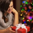 Happy young woman near christmas tree holding present box — Stock Photo