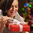 Happy young woman opening present box in front of christmas ligh — Stock Photo