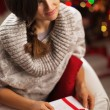 Portrait of young woman with postcard in front of christmas ligh — Stockfoto