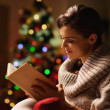 Happy young woman reading book in front of christmas tree — ストック写真