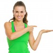 Smiling fitness young woman presenting something on empty palm — Stock Photo #30054379