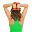 Fitness young woman making exercise with dumbbells . rear view — Stock Photo