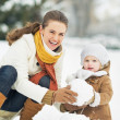 Happy mother and baby making snowmin winter park — Stock Photo #30058975