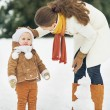 Mother and baby playing in winter outdoors — Stock Photo