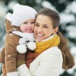 Portrait of smiling mother and baby in winter park — Stock Photo #30059243