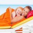 Stock Photo: Portrait of smiling mother and baby laying on sunbed