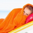 Young woman wrapped in towel laying on chaise-longue — Stock Photo