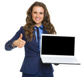 Smiling business woman showing laptop blank screen and thumbs up — Stock Photo