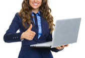 Closeup on business woman with laptop showing thumbs up — Stock Photo