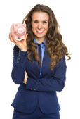 Smiling business woman showing piggy bank — Photo