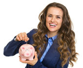 Sorridente donna d'affari, mettendo le monete nel salvadanaio — Foto Stock