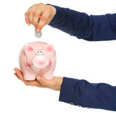 Closeup on business woman hands putting coin into piggy bank — Stok fotoğraf