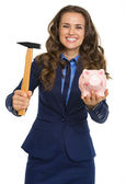 Smiling business woman giving piggy bank and hammer — Stock Photo