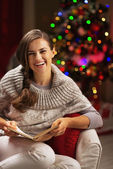 Happy young woman reading book near christmas tree — Stock Photo