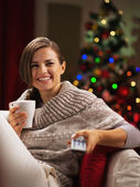 Happy young woman with cup of hot beverage near christmas tree w — Stock Photo