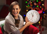 Smiling young woman near christmas tree showing clock — Stock Photo