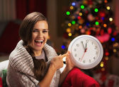 Smiling young woman near christmas tree pointing on clock — Stock Photo