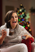 Surprised young woman with cup of hot chocolate watching tv — Stock Photo