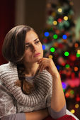 Portrait of thoughtful young woman in front of christmas lights — Stock Photo