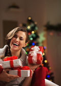 Happy young woman sitting in front of christmas tree — Stock Photo