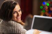 Glückliche junge frau mit laptop vor weihnachtsbaum — Stockfoto