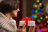 Happy young woman with present box in front of christmas lights — Stock Photo