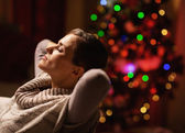 Relaxed young woman sitting in armchair in front of christmas tr — Stockfoto